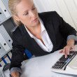 Woman with calculator in office — Stock Photo