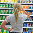 Woman in front of shelves in the supermarket — Stock Photo #32659801