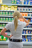 Woman in front of shelves in the supermarket — Stok fotoğraf