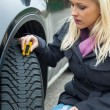 Woman measures tire tread of a car tire — ストック写真
