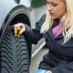 kadın tedbirler lastiği araba lastiği basmak — Stok fotoğraf
