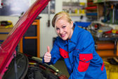 Woman as a mechanic in auto repair shop — Stok fotoğraf