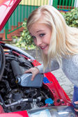 Woman filling oil into car — Stock Photo