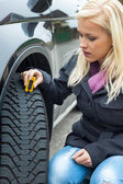 Woman measures tire tread of a car tire — Stok fotoğraf