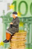 Pensioner sitting on cash pile — Stock Photo