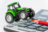 Tractor, red pen and calculator — Stock Photo
