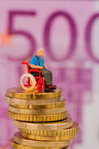 Woman in wheelchair on money stack — Stock Photo