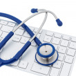 Stock Photo: Stethoscope and keyboard of computer