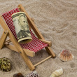 Stock Photo: Beach chair with piggy bank and dollars