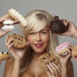 Woman eating cream cakes — Stockfoto