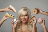 Woman eating cream cakes — Stock Photo