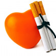 Stock Photo: Orange heart, three cigarettes, isolated on white background.