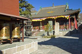 Prayer wheels and incense burner in the courtyard of the monastery in Wutai — Stock Photo