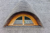 Semi-circular window in the roof of straw — Stock Photo
