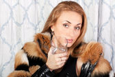 Young brunette woman with a glass — Stock Photo