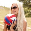 Cheerful blond girl in black bikini with a ball outdoor — Stock Photo