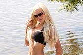 Lovely smiling blond girl in bikini on the beach — Stock Photo