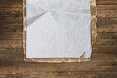 Zerrissenes papier auf einem hölzernen hintergrund — Stockfoto