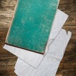 Book and vintage paper sheets on wood — Stock Photo
