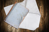 Aged book and wrinkled papers on a wood — Stock Photo