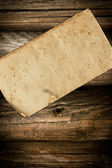 Dark faded blank paper on a wooden background — Stock Photo