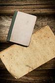 Livre fanée et papier sur un fond en bois — Photo