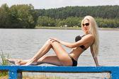 Verleidelijke blonde vrouw in bikini op het meer — Stockfoto