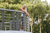 Young lovely blond girl in the park — Stock Photo