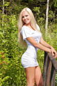 Slim smiling blond lady in a dress outdoor — Stock Photo