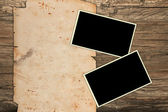 Aged photo frames and paper on wood — Stock Photo