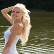 Foto Stock: Cheerful blond girl at the lake