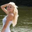 Stock fotografie: Cheerful blond girl at the lake