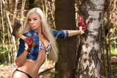 Sexy blond model with an axe in the forrest — Stock Photo