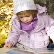 Girl reads a book in an autumn park — Stock Photo
