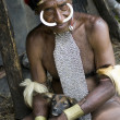 The man of a Papuan tribe in traditional clothes and coloring in - Stock Photo