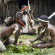 Warriors of a Papuan tribe in traditional clothes and coloring - Stock Photo