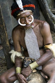 The man of a Papuan tribe in traditional clothes and coloring in — Stock Photo
