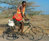 African man in traditional clothes rides a bicycle — Stock Photo