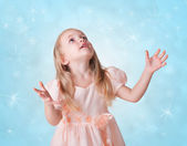 Little girl on blue background with snowflakes — Stock Photo
