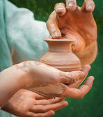 Close-up of hand holding pottery an jar — Stock Photo