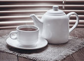 Tea cup with teapot on old wooden table — Stock Photo