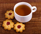 tea cup with flowers cookie on wooden background — Стоковое фото
