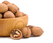 Wooden bowl full of walnuts on white background  — Stock Photo