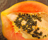Fresh ripe juicy papaya slice on wooden background — Foto Stock