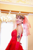 The beautiful bride in a red dress — Stock fotografie
