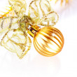 New Year's gold ball with a bow and New Year's tinsel. — Stock Photo