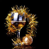 Glass with drink, a Christmas ball and tinsel. — Stock Photo