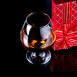 Glass with alcohol and a gift. — Stock Photo