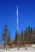 Snow-covered tower repeater mobile communication against the blue sky — Stock Photo
