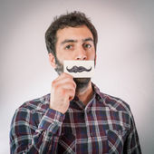 Young man with fake self moustaches — Stock Photo